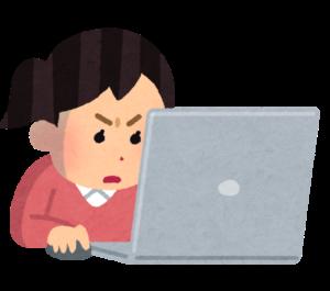 真剣にパソコンで物件を探す女性